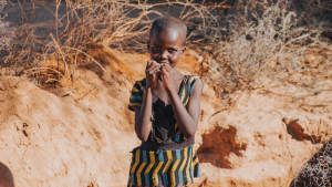 An orphaned African child, looking for water to drink.