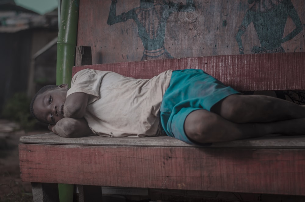 An orphaned African child, sleeping on a bench thirsty.