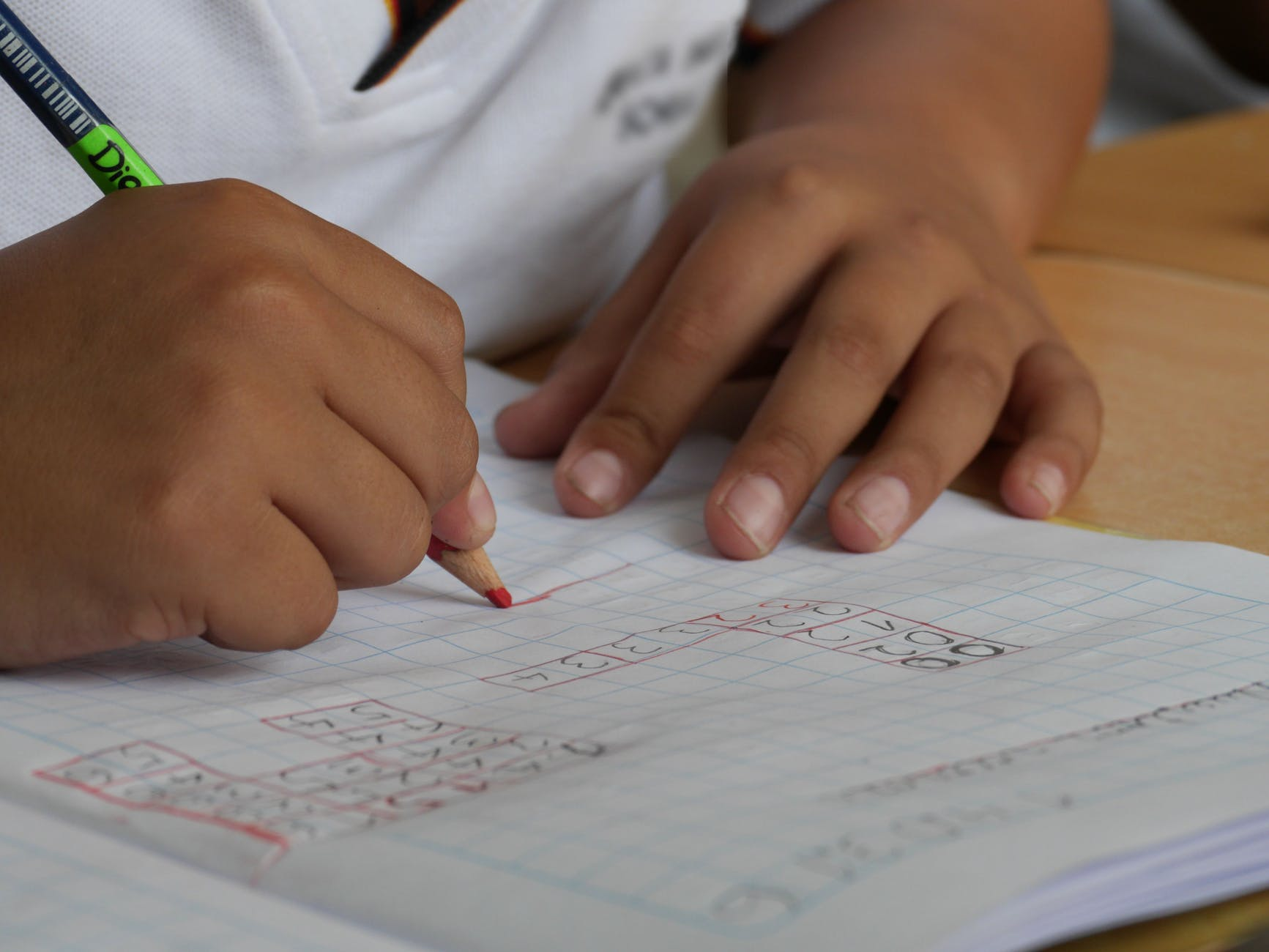 a child writing in a notebook with classroom supplies