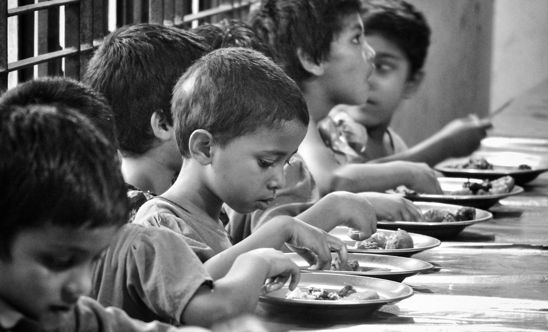 A black and white picture of children eating in an orphanage