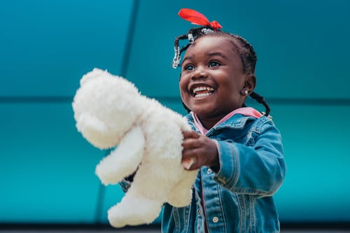 A little girl playing with a stuffed toy