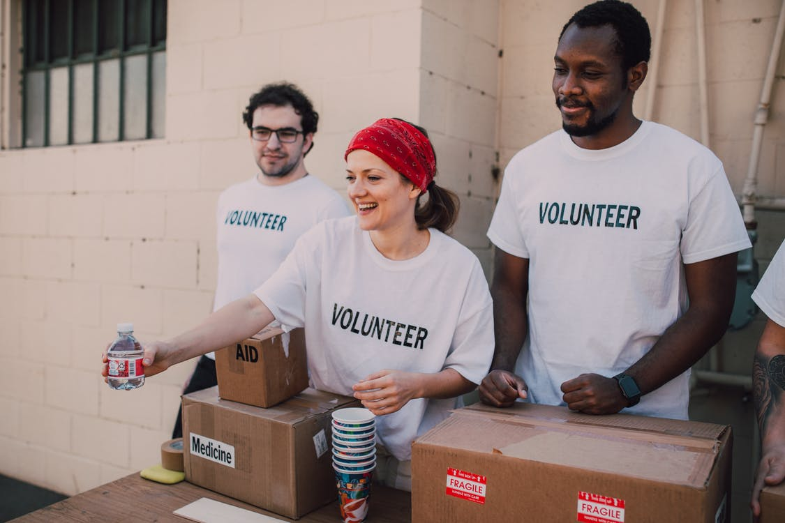 Three people doing volunteer work
